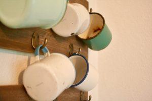 vintage enamelware cups arranged on hooks
