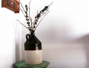 a vintage crock filled with faux greenery