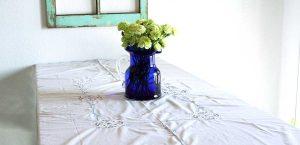 a vintage blue vase filled with green flowers