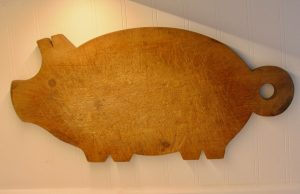 antique wooden pig shaped cutting board on a wall