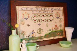 vintage cross stitch sampler with jadeite and milk glass