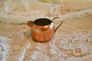copper creamer displayed on a lace cloth