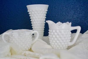 a grouping of white hobnail glass