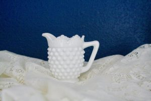 white hobnail creamer displayed on a lace cloth