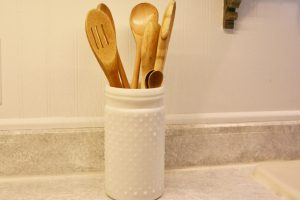 tall hobnail jar holding wooden spoons
