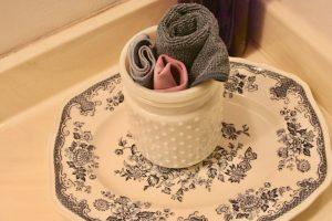 small white hobnail jar as towel storage