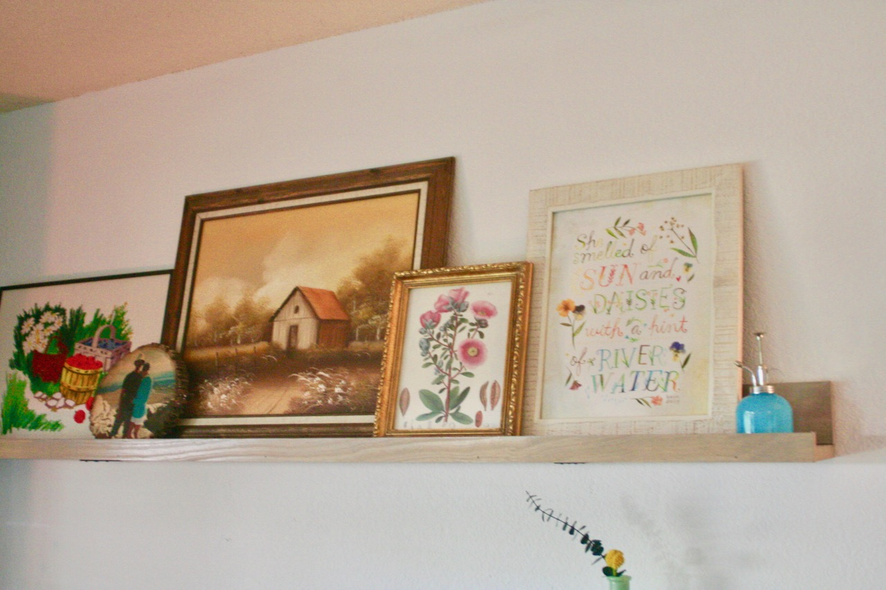 vintage art displayed on a picture rail