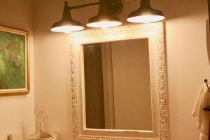 a vintage wooden mirror hanging in a bathroom