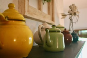a collection of vintage colored enamelware teapots