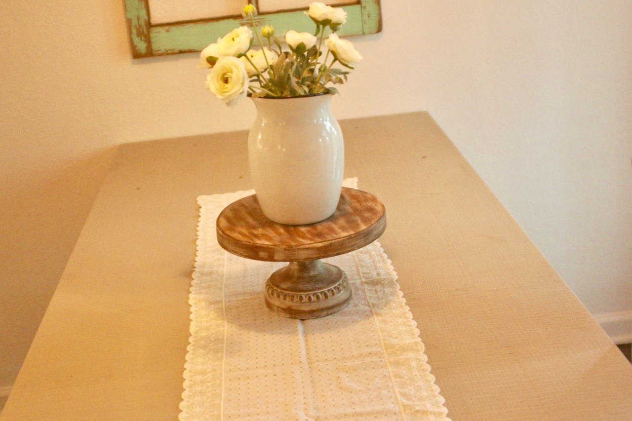 a vintage lace table runner with an enamelware vase