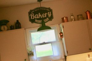 a kitchen filled with vintage copper and green accents