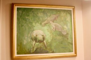 a vintage canvas painting with manatees displayed in a bathroom