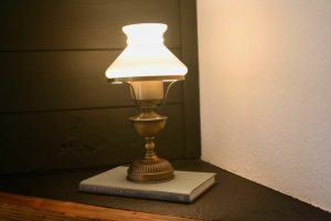 a vintage lamp with a white milk glass shade on top of a book