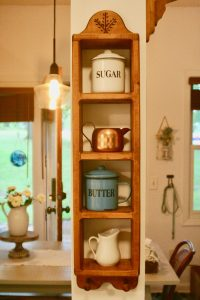 a wooden shelf displayed with vintage kitchen decor