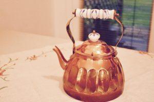 vintage copper teapot on vintage linen