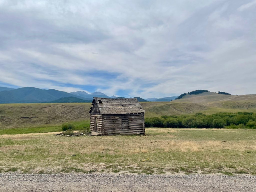 an old worn log cabin in the mountains