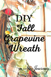 fall grapevine wreath displayed on a vintage window