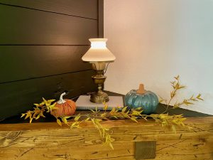 fall decor on a mantel with pumpkins