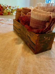 vintage wooden cheese box as storage for cloth napkins