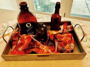vintage amber colored bottles amongst plaid fabric