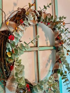 a diy grapevine wreath hanging on an old window