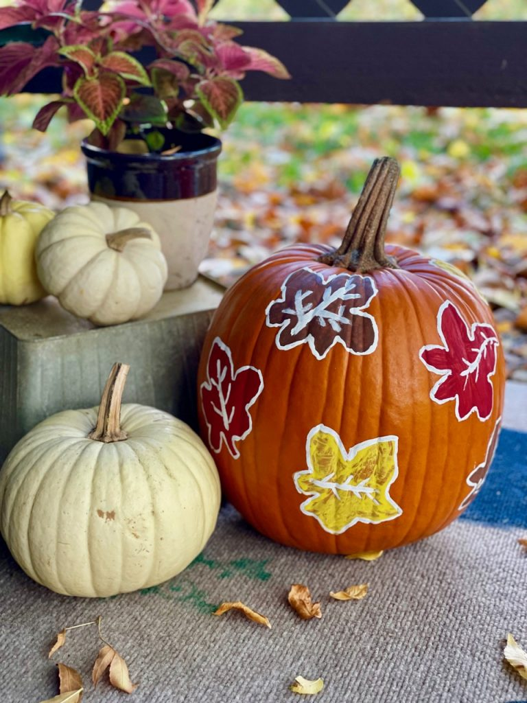 a diy stenciled pumpkin displayed with white pumpkins